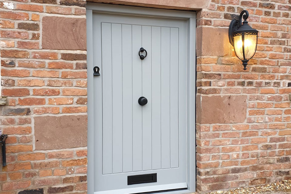 Grey blue painted barn style front door with black door furniture fitted in Nantwich Cheshire