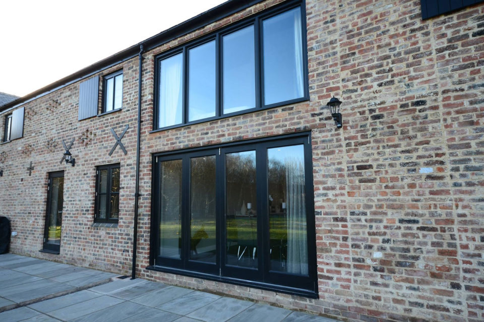 Accoya timber bi-folding doors and windows in a black paint pre finish