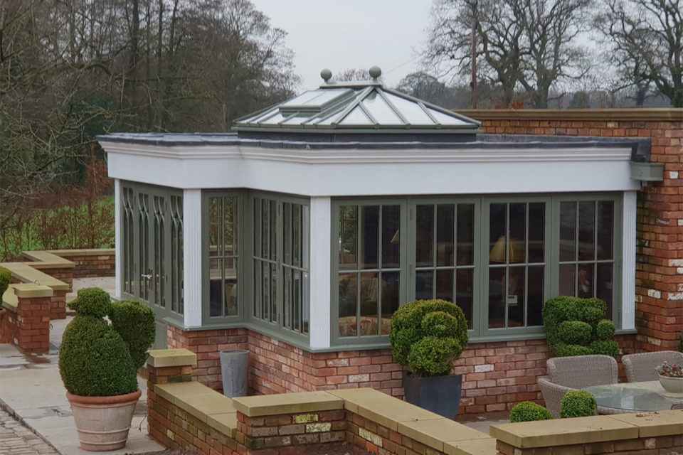green orangery with roof lantern, casement windows and French doors